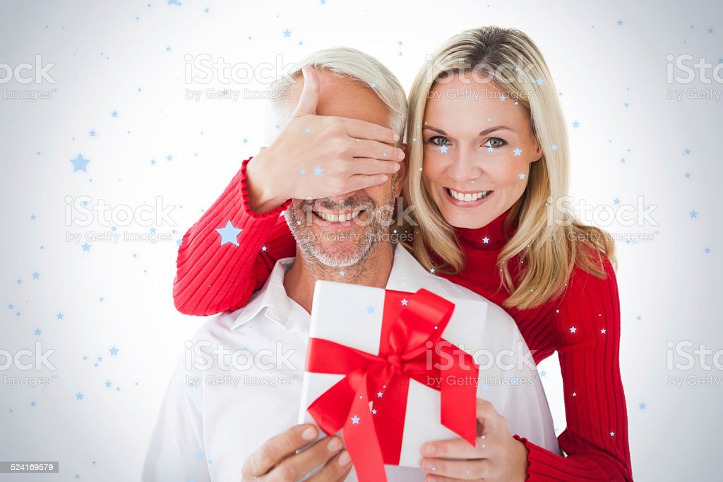 Smiling woman covering partners eyes and holding gift stock photo