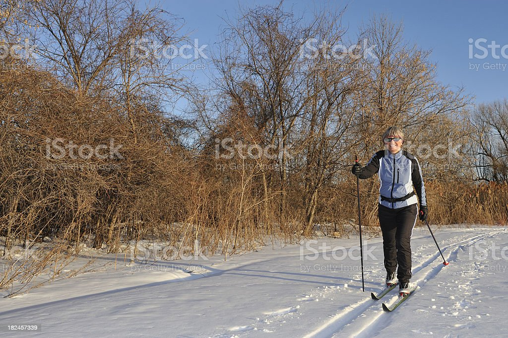 Mature woman skiing. Late afternoon light. Fluorescent strips on the...