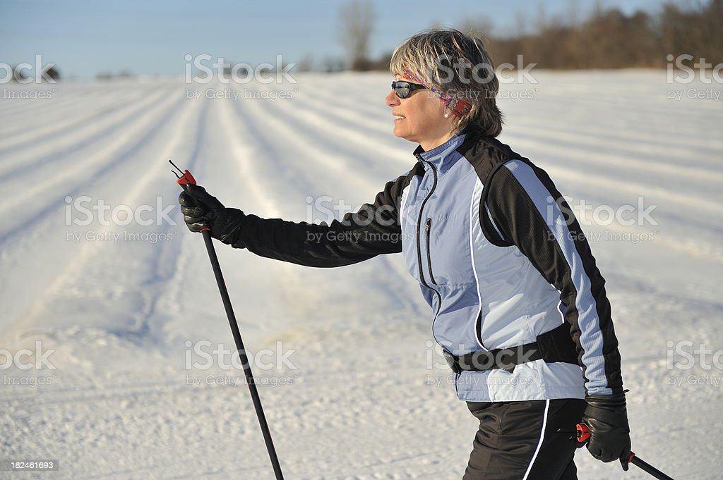 Active mature woman skiing in late afternoon light. Fluorescent...