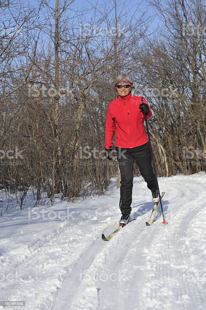 Mature woman skiing. Fluorescent stripes on pants sides.