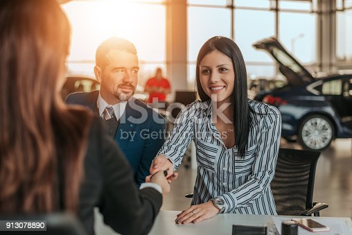 istock Smiling woman customer shaking hands with car dealer. 913078890