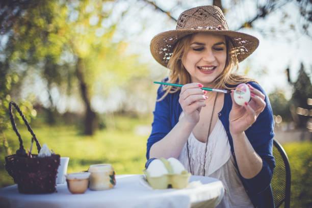 lächelnde frau dekoration ostern eiern an einem schönen sonnigen tag - schöne osterbilder stock-fotos und bilder
