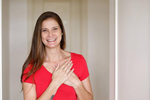 smiling woman doing social distance greeting - mão no peito imagens e fotografias de stock