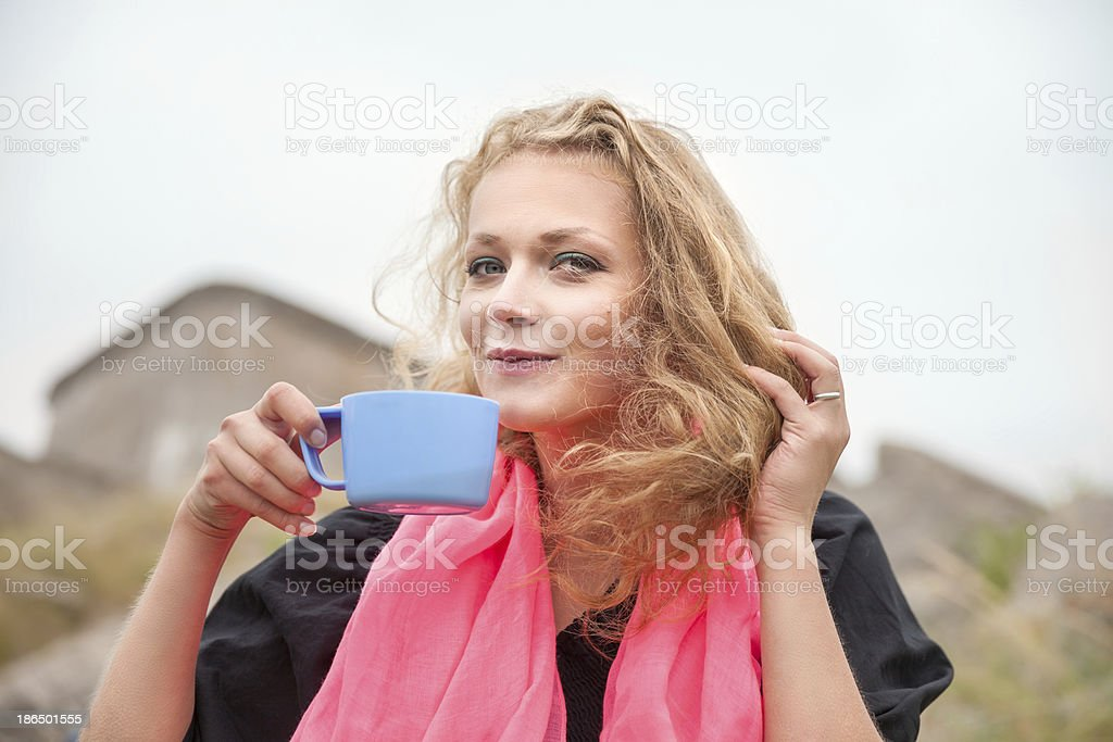 smiling woman drinking coffee outdoors royalty-free stock photo