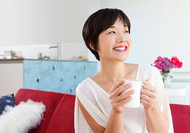 Smiling woman drinking cup of coffee stock photo