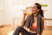 Smiling woman drinking orange juice after sports training.