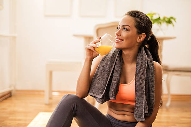 smiling woman drinking orange juice after sports training. - drinking juice stock photos and pictures
