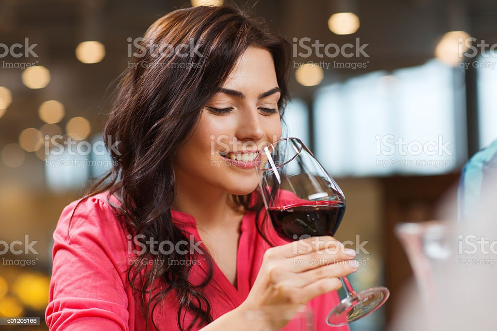 smiling woman drinking red wine at restaurant stock photo