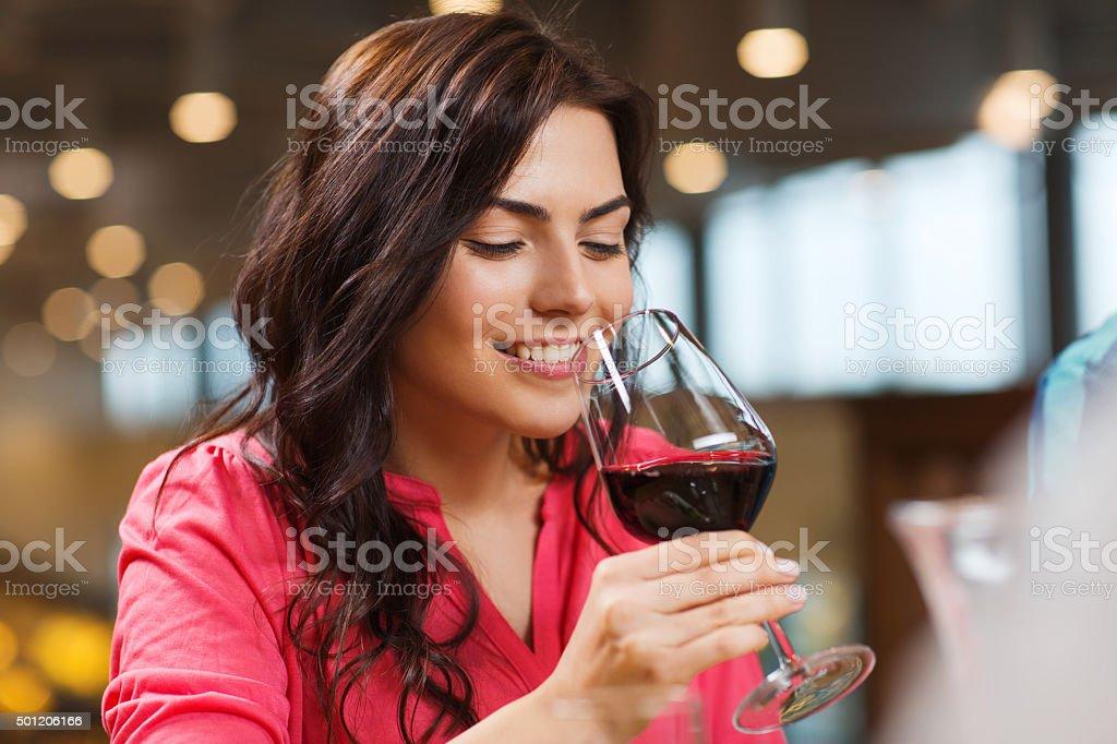 Mulher sorridente bebendo vinho tinto no restaurante - foto de acervo