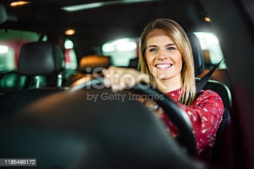 Smiling woman driving a car in public garage.