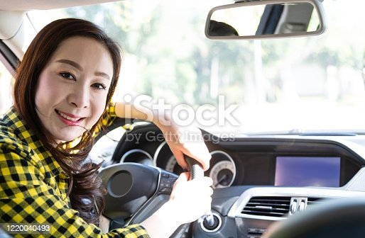 627864748 istock photo Smiling woman driving in a car 1220040493