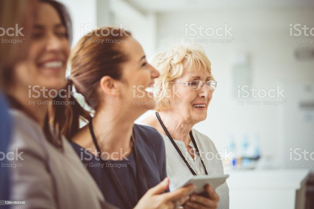 Smiling woman during a seminar Smiling woman with digital tablet sitting in audience during seminar. Group of women attending a seminar. Adult Stock Photo