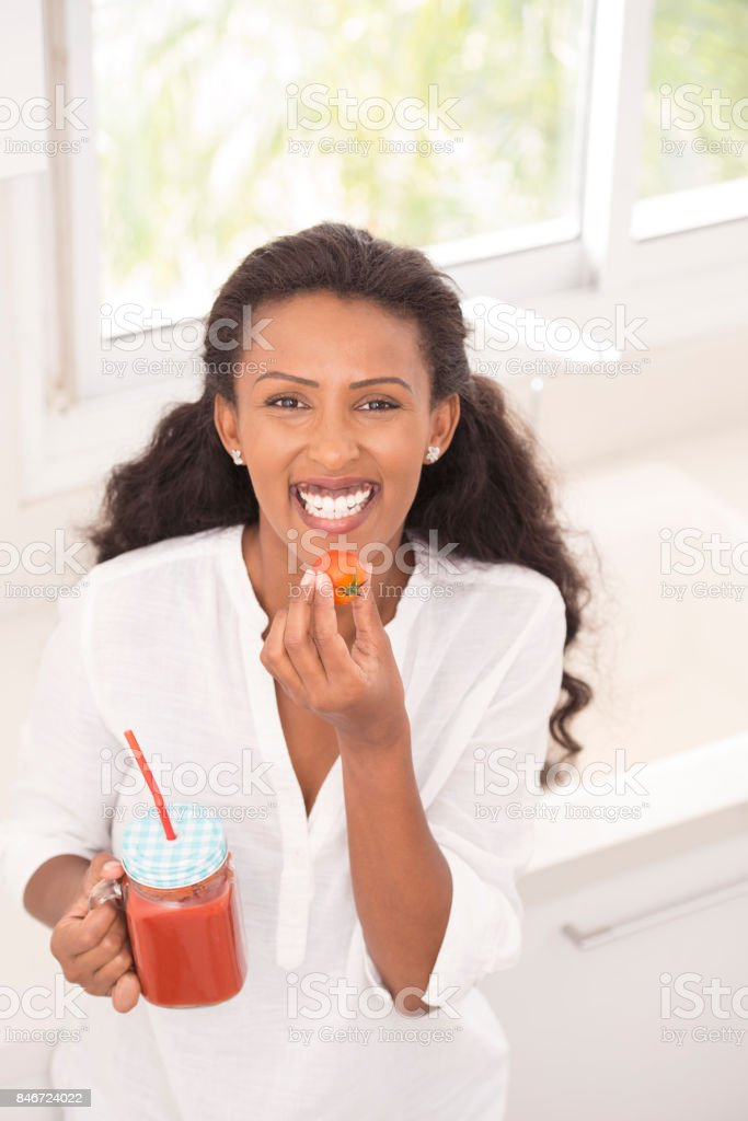 Smiling woman eating and drinking tomato. stock photo