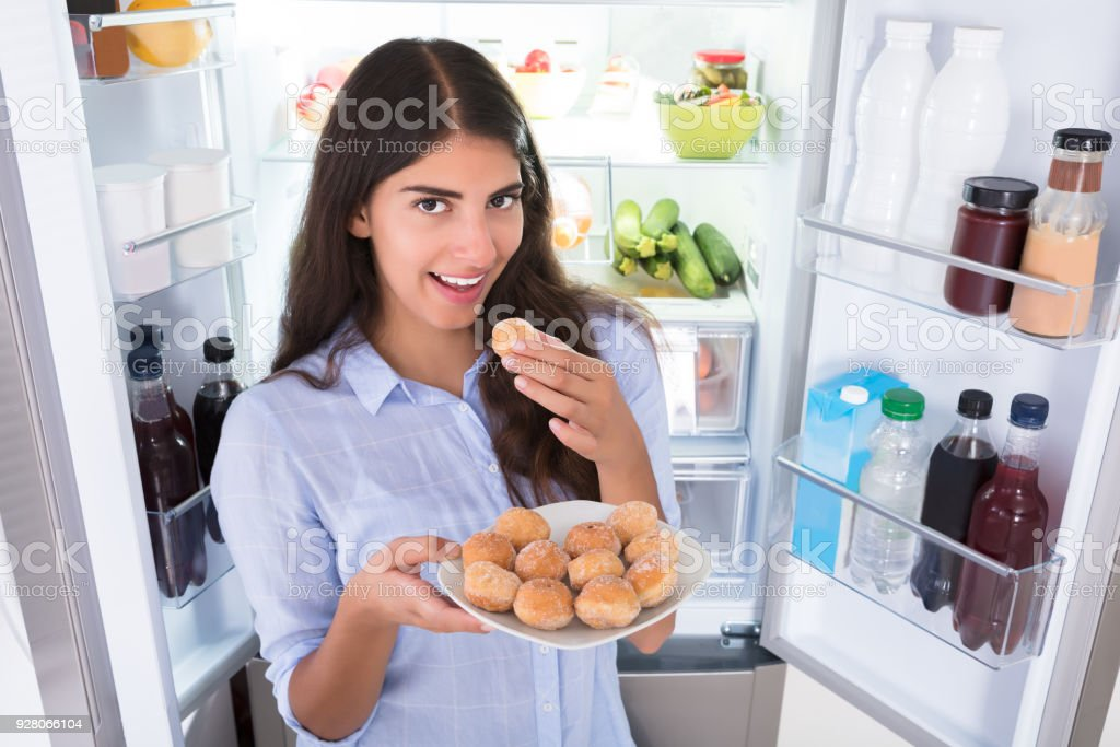 Smiling Woman Eating Cookies In Plate stock photo