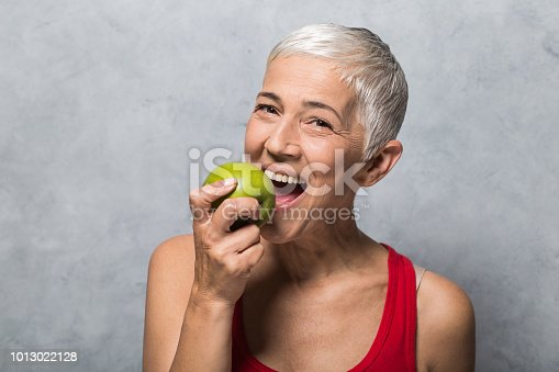 istock Smiling woman eating green apple 1013022128