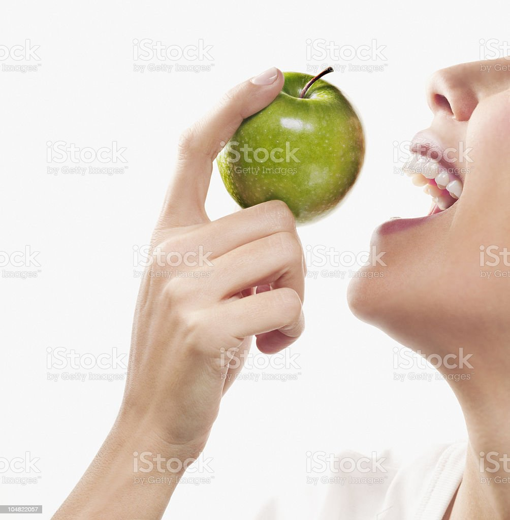 Smiling woman eating green apple royalty-free stock photo