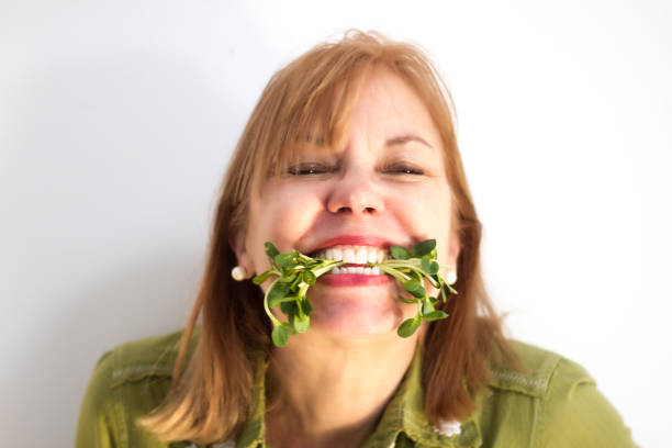 Smiling Woman Eating Raw Super Sprouts (Close-Up) stock photo