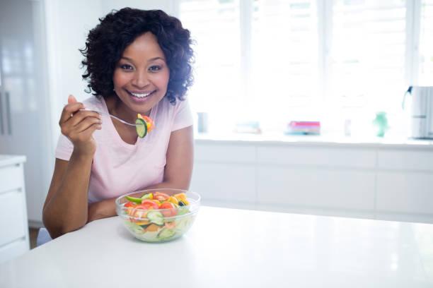 lachende vrouw salade eten in de keuken - mid volwassen stockfoto's en -beelden