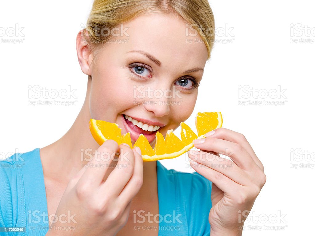 smiling woman eats the fresh orange royalty-free stock photo