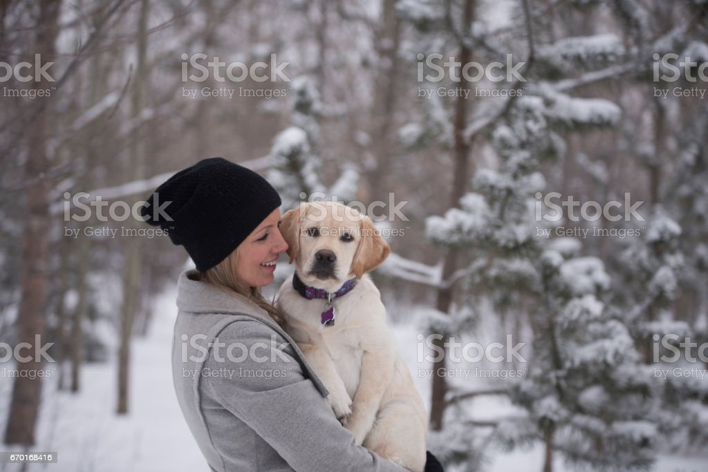 Smiling woman embraces healthy puppy who leans into her looking at the camera stock photo