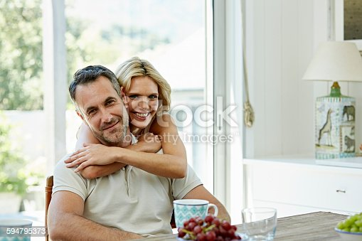 Portrait of smiling woman embracing man from behind at home