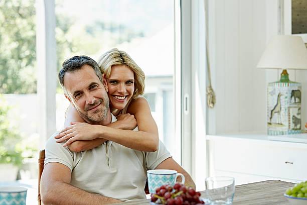smiling woman embracing man at home - 35 39 jahre stock-fotos und bilder