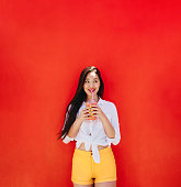 Cheerful asian woman drinking juice in a disposable glass. Woman having a refreshing smoothie using a straw.