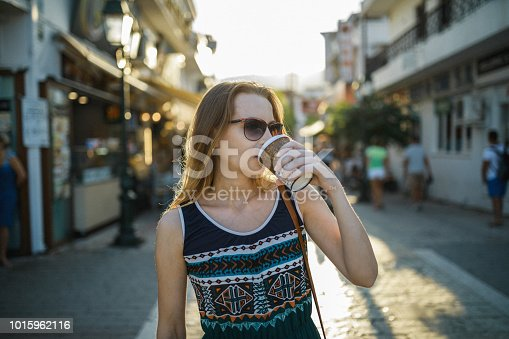 Smiling woman enjoying coffee to go during her summer vacation