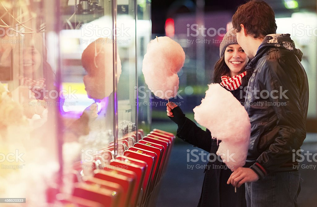 Smiling woman enjoying cotton candy with man royalty-free stock photo