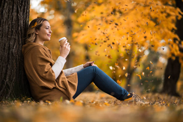 Smiling woman enjoying in coffee at the park. stock photo
