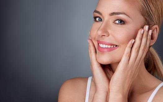 istock Smiling woman enjoying in her healthy skin 664431998
