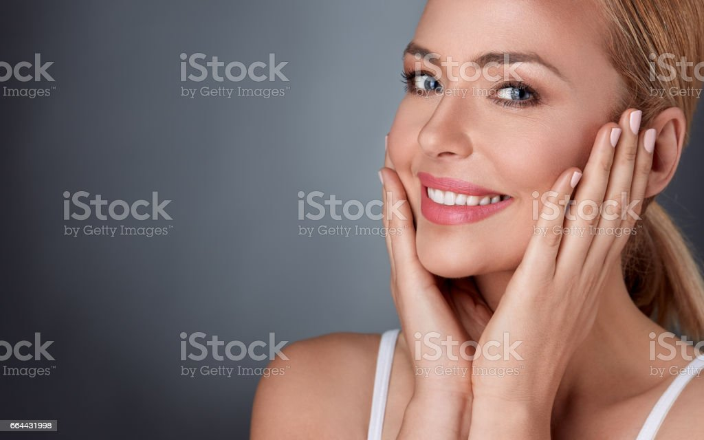 Smiling woman enjoying in her healthy skin stock photo