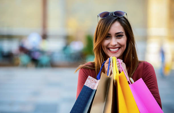 Smiling woman enjoying in shopping. Consumerism, fashion, lifestyle concept stock photo