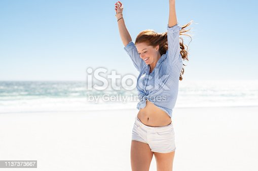 Happy mature woman in blue blouse and white shorts enjoying tropical beach vacation. Smiling young woman having fun on her vacation at sea. Joyful lady with red hair enjoying freedom with outstreched arms, jumping on beach with copy space.