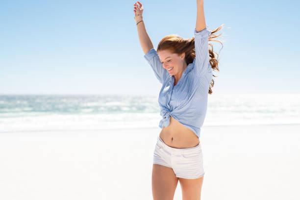 donna sorridente che si gode la spiaggia - il corpo umano foto e immagini stock
