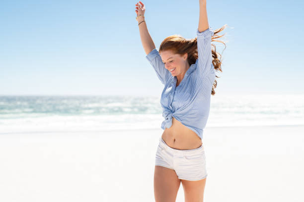 Smiling woman enjoying the beach Happy mature woman in blue blouse and white shorts enjoying tropical beach vacation. Smiling young woman having fun on her vacation at sea. Joyful lady with red hair enjoying freedom with outstreched arms, jumping on beach with copy space. the human body stock pictures, royalty-free photos & images