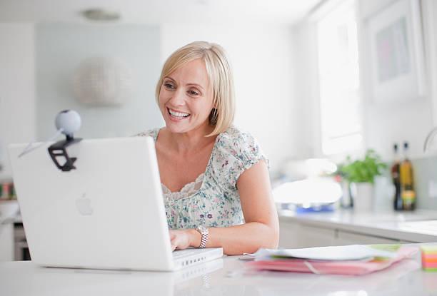 Smiling woman enjoying video chat on laptop stock photo