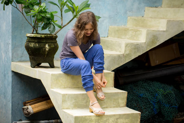 Smiling woman fastening sandals sitting on stairs stock photo