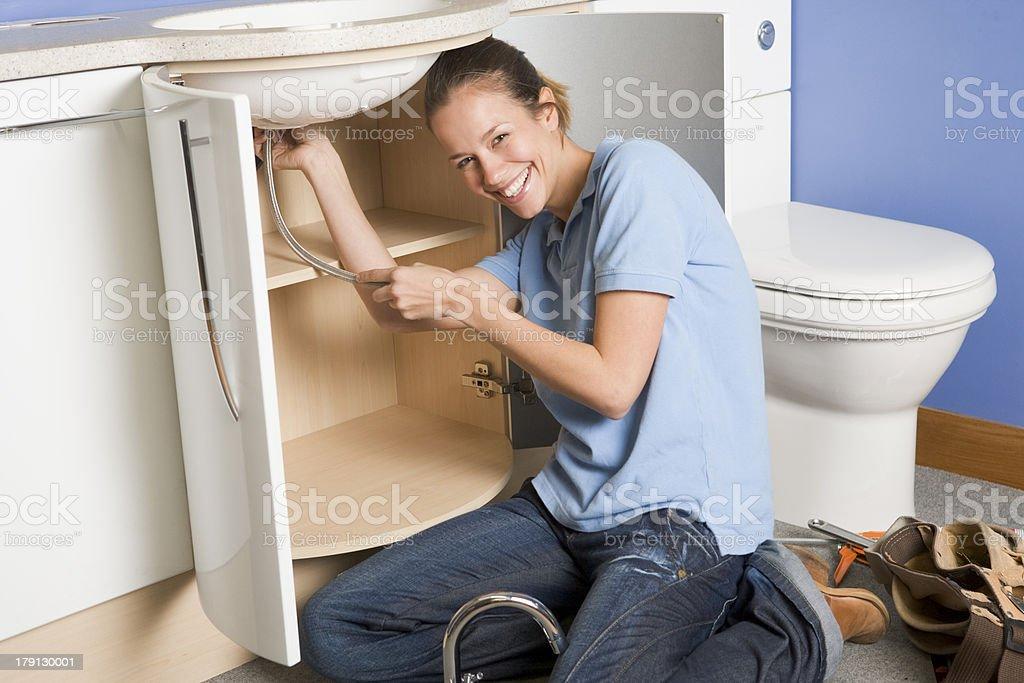Smiling woman fixing plumbing in bathroom sink royalty-free stock photo