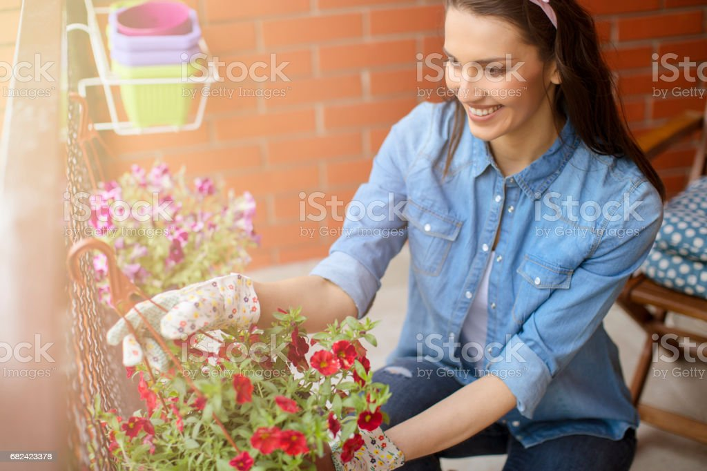 Smiling woman gardening on a balcony royalty-free stock photo