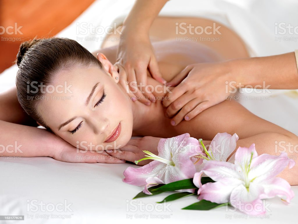 Smiling woman getting a massage in a spa stock photo