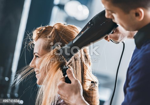 Young hairdresser drying customers hair with round brush at hair salon.