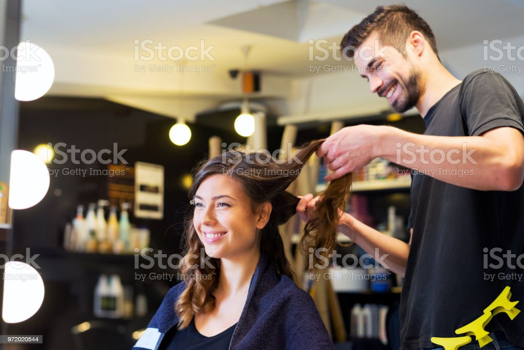 Smiling Woman Getting New Hairstyle In The Hair Salon Stock Photo