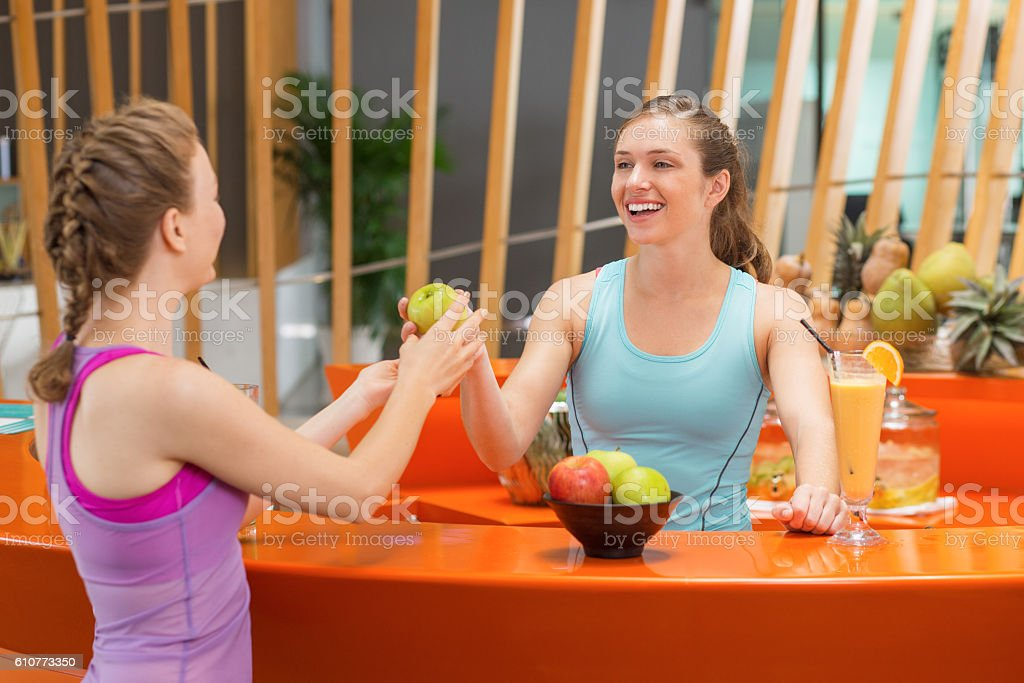 Smiling Woman Giving Apple to Her Sport Friend stock photo
