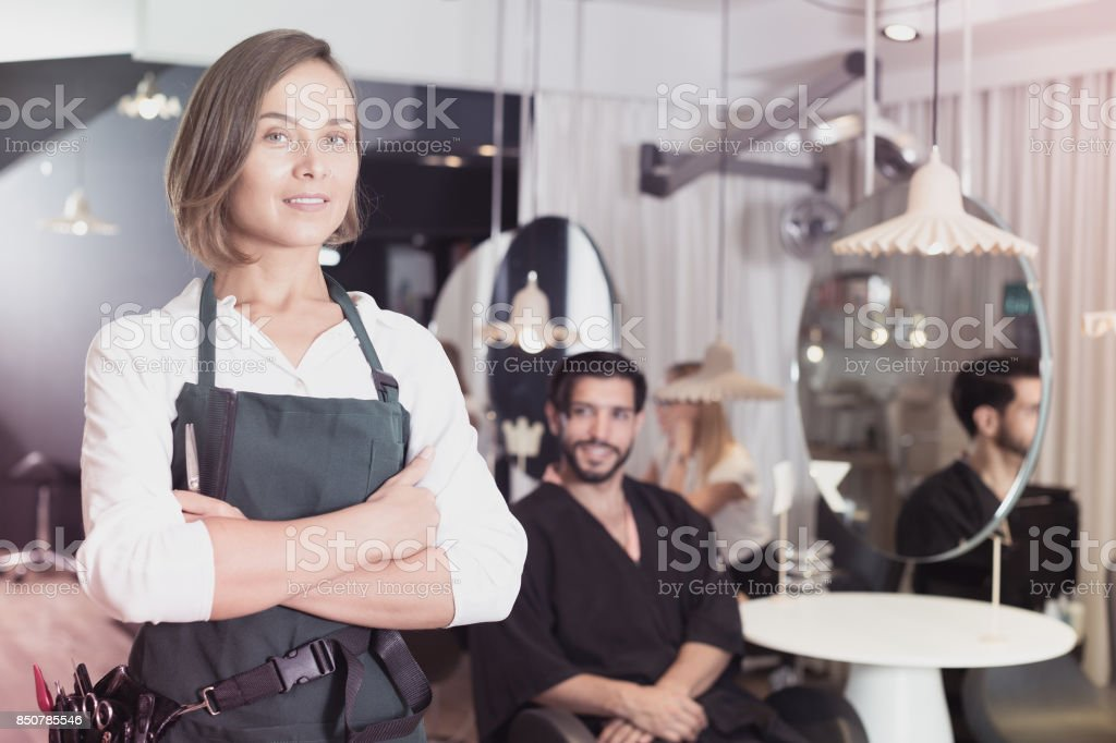 smiling woman hairdresser with male visitor stock photo