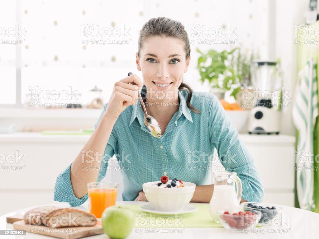 Mulher sorridente com pequeno-almoço em casa - foto de acervo
