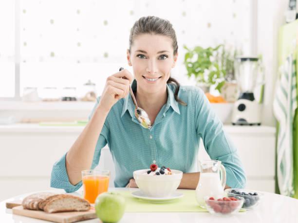 sonriente mujer desayunando en casa - fibra dietética fotografías e imágenes de stock