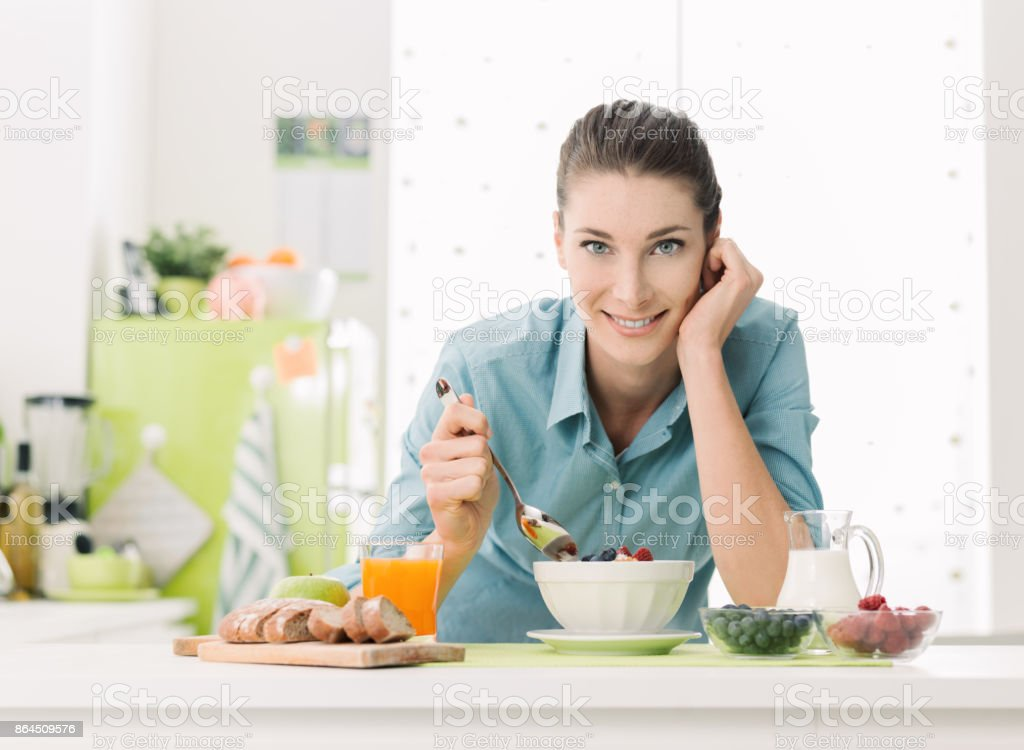 Smiling woman having breakfast at home stock photo