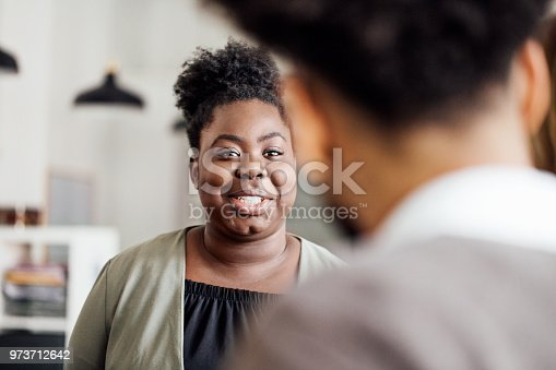 Smiling young woman talking with male colleague in office. African female having a friendly talk with coworker.