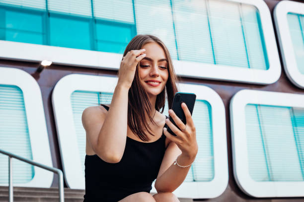Smiling woman having mobile phone video call sitting on urban stairway stock photo